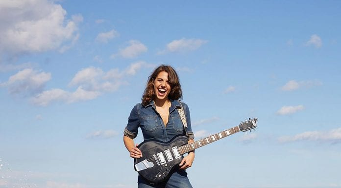 rachel ana dobken holding guitar on beach rocks