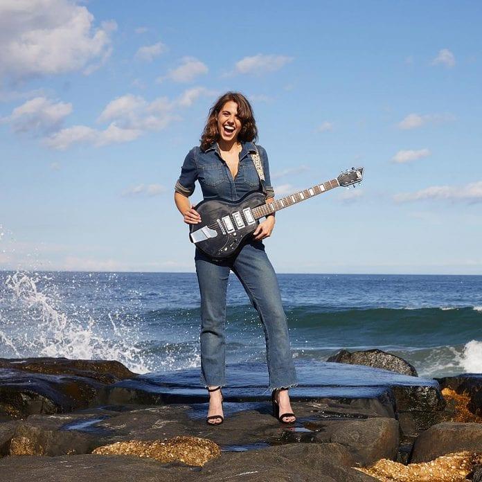 rachel ana dobken holding guitar on beach rocks