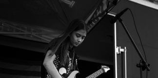girl on stage playing guitar