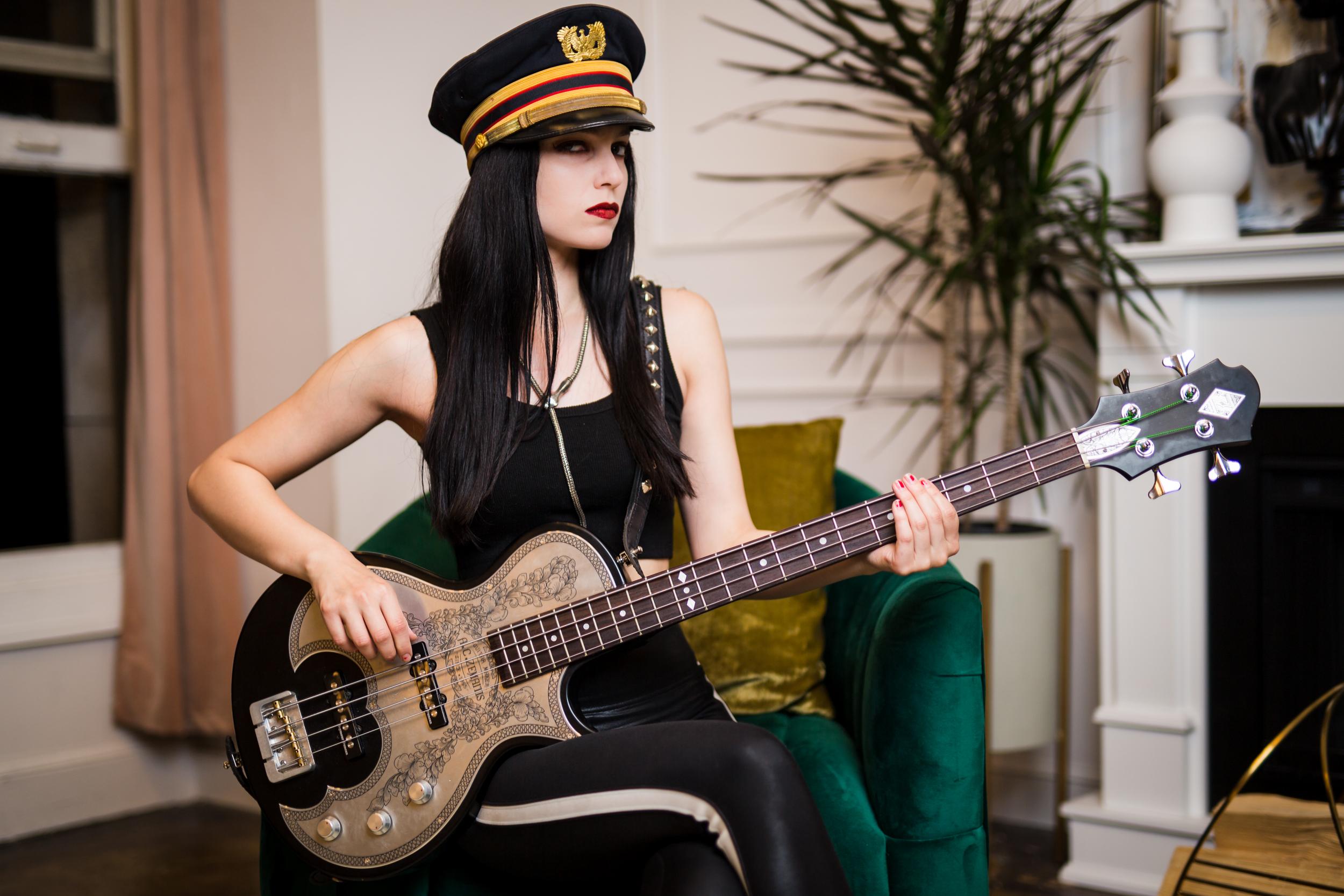 girl sitting down holding guitar